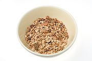 Granola Cereal (rolled oats with dried fruits and nuts) in a bowl on white background