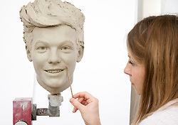 "© Licensed to London News Pictures. 19/02/2013. London, UK Sculptor Georgina Power works on the clay head of Louis Tomlinson. Madame Tussauds today released pictures of sculptors working on the life-like clay heads of the five members of pop band ""One Direction ' The clay heads will be used to create the moulds for their new wax figures.  Niall, Liam, Louis, Harry and Zayn have been closely involved in the creation process giving the creative team two sittings at which hundreds of measurements were taken to ensure total accuracy.   The clay heads will now be used to make the moulds for the final wax figures, which will be revealed in London. Photo credit : Madame Tussauds /LNP"
