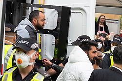Glasgow, Scotland, UK. 13 May 2021.At approx 5.30 pm police released two men from a Home Office detention vehicle. Accompanied by lawyer Aamer Anwar the men walked to a nearby mosque surrounded by hundreds of police and supporters who had previously been surrounding the vehicle and sitting on the street. Two males are released from the vehicle accompanied by Aamer Anwar. Iain Masterton/Alamy Live News