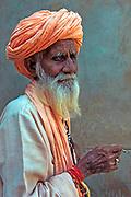 Portrait of a local camel farmer smoking a bidi cigarette, Pushkar Camel Fair, Rajasthan