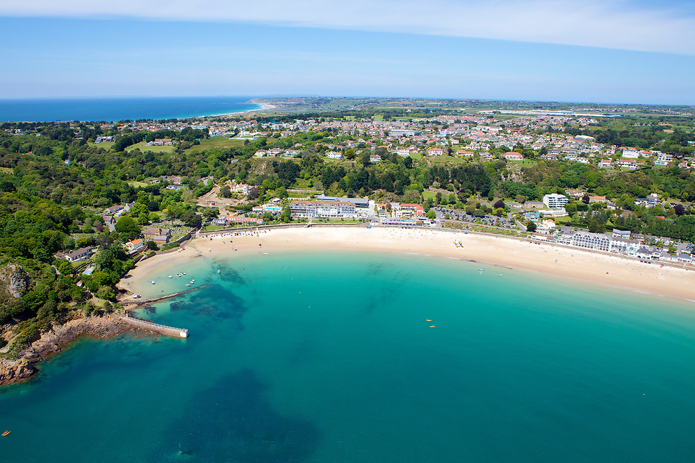 Aerial view of people and tourists enjoying the beautiful beach of St Brelade's Bay with its golden sands and turqiouse clear water in Jersey, Channel Islands