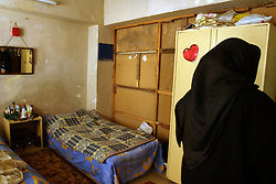 An Iraqi girl, is seen in the bedroom where she says her brother was beat up by US troops in Baghdad, Iraq, Feb. 22, 2004. She also said she paid a $25,000 bribe to several Americans in civilian clothes who were carrying weapons, to erase the criminal records of her father and brother who are in prison at Abu Ghraib. She too was struck by an American soldier with the butt of his machine gun as he entered their apartment during a raid of their home.