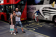 Hugging couple and urban cyclist leaning against a tour coach in central London. Unaware of the theatre behind them, the an and woman hug each other for someone else's photo. The cyclist is taking his life in his own hands by wishing to squeeze between the large vehicles on this busy street in the capital.