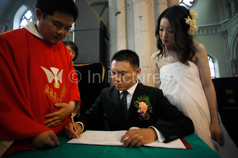 Coca Dai and Juan Juan sign a document during their wedding ceremony at the Xujiahui Catholic Church in Shanghai, China on 23 May 2009. A hip street artist and a recent Catholic convert, Mr. Dai is one of many young Chinese embracing religion, perhaps to fill the lack of belief and ideology in an authoritarian communist China that embraces the most extreme form of capitalism in practice. The Chinese government and the Vatican have a long history of simmering mutual distrust and suspicion, as two parties compete for the control of the Chinese Catholic church, with some 15 million and growing number of faithfuls.  Overall Christians now number over 110 million in China, which makes it the third largest Christian nation in the world.