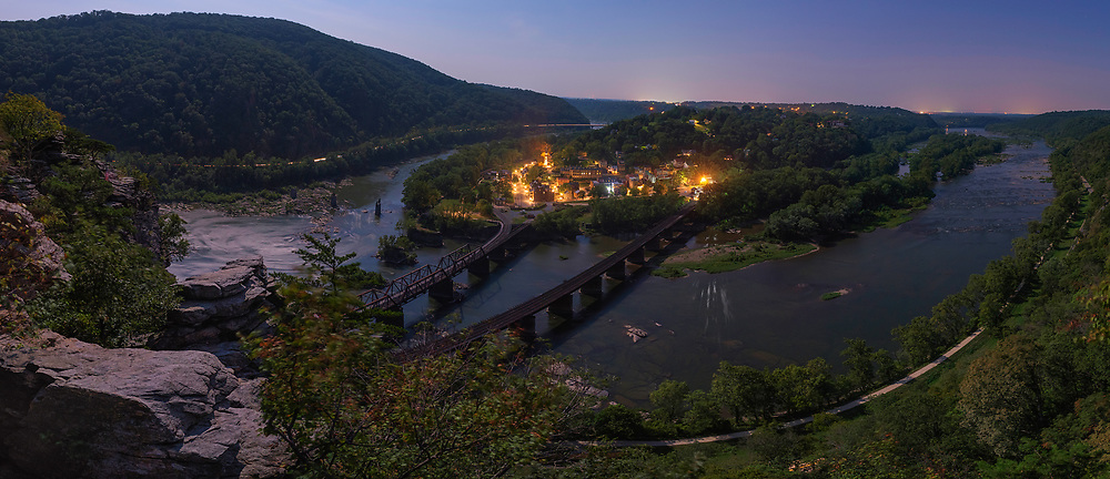 """The historic town of Harpers Ferry is illuminated from a full moon above; as seen from the edge of Maryland Heights.<br /> <br /> On the night of October 16th, 1859 a party of 17 armed men led by the militant abolitionist John Brown crossed the Potomac River over the B&O railroad bridge (the piers of which can be seen below at left) to seize the federal arsenal at Harpers Ferry and its stockpile of 100,000 rifles and muskets. With these weapons, Brown intended to facilitate an armed slave uprising that would spread throughout the entire South. <br /> <br /> While his raid failed, the news of John Brown's attempt was an earthquake that reverberated throughout the entire Union and split the fault line between North and South. denounced as a psychotic terrorist by Southerners, Brown was embraced by many Northern abolitionists as a martyr. This outpouring of support for Brown exasperated Southern suspicions of a yankee-abolitionist plot to subjugate the South under Northern control through emancipation; by force if necessary. Southern states, long fearful of slave revolts, revived the militia system to combat all future """"John Browns"""" laying the foundation for what would become the Confederate Army. <br /> <br /> On the morning of his execution, John Brown handed a note to one of his guards that would become prophetic: """"I, John Brown, am now quite certain that the crimes of this guilty land will never be purged away but with blood..."""" 16 months later, Confederate batteries in Charleston would open fire on Fort Sumter, and the bloody purge would begin."""