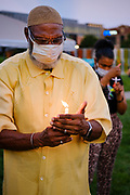 21 JULY 2020 - DES MOINES, IOWA: Iowa State Representative AKO ABDUL-SAMAD holds a candle during a memorial and vigil for  Representative John Lewis (D-GA). About 300 people attended the vigil for Congressman Lewis in Poppajohn Sculpture Park in Des Moines Tuesday night. Rep. Lewis died from pancreatic cancer on July 17, 2020.             PHOTO BY JACK KURTZ
