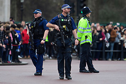 © Licensed to London News Pictures. 21/12/2016. London, UK. Extra armed police officers watch over during road closures in place around Buckingham Palace in London at the time of Changing of the Guard ceremony. The extra closures have come in to place following a terrorist attack using a vehicle in Berlin.  Photo credit: Ben Cawthra/LNP