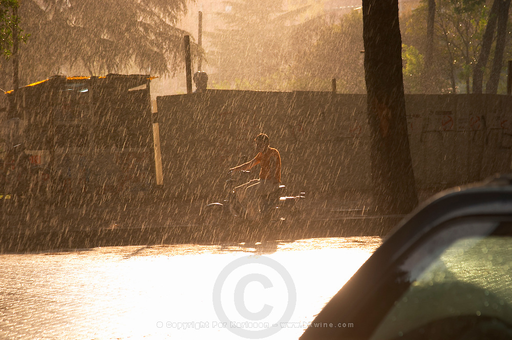 Man on a moped on a rainy street in sunshine. Tirana capital. Albania, Balkan, Europe.