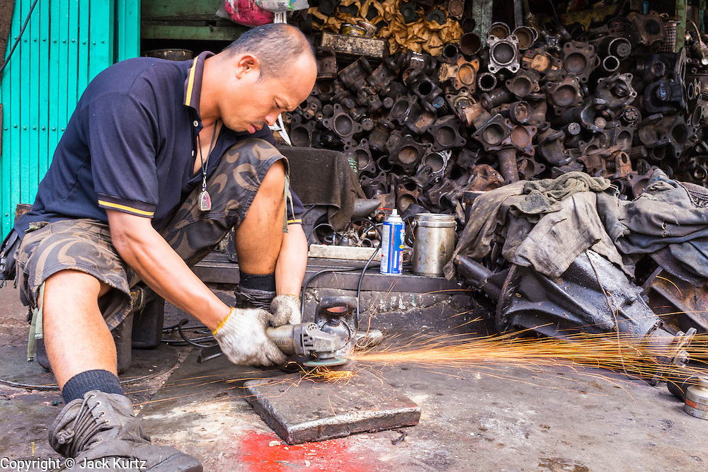 27 APRIL 2013 - BANGKOK, THAILAND:   Sparks fly off of a grinding wheel being used at a mechanical shop in Talat Noi. The Talat Noi neighborhood in Bangkok started as a blacksmith's quarter. As cars and buses replaced horse and buggy, the blacksmiths became mechanics and now the area is lined with car mechanics' shops. It is one the last neighborhoods in Bangkok that still has some original shophouses and pre World War II architecture. It is also home to a  Teo Chew Chinese emigrant community.         PHOTO BY JACK KURTZ