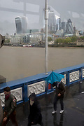 Tourists brave a wet and windy Tower Bridge, on Tower Bridge, on 8th May 2019, in London, England.