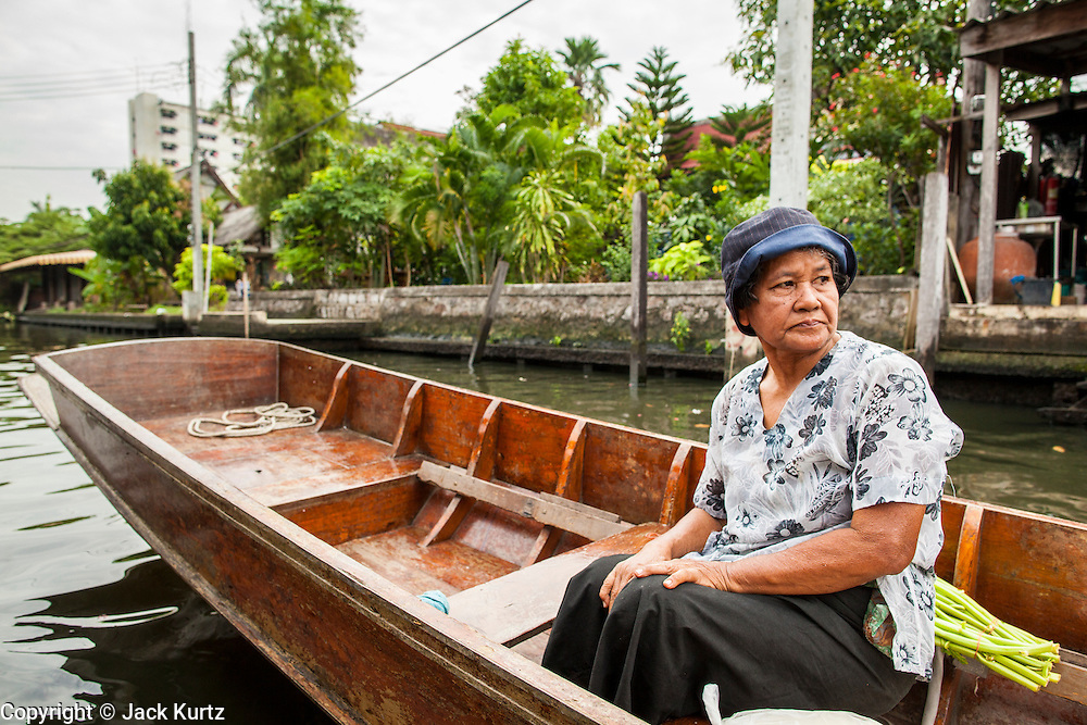 """17 NOVEMBER 2012 - BANGKOK, THAILAND:  A woman on a """"long tailed"""" boat in Bangkok. Long tailed boats use big V8 car engines and have 30-40 foot long propeller shafts that extend past the back of the boat. Bangkok used to be known as the """"Venice of the East"""" because of the number of waterways the criss crossed the city. Now most of the waterways have been filled in but boats and ships still play an important role in daily life in Bangkok. Thousands of people commute to work daily on the Chao Phraya Express Boats and fast boats that ply Khlong Saen Saeb or use boats to get around on the canals on the Thonburi side of the river. Boats are used to haul commodities through the city to deep water ports for export.    PHOTO BY JACK KURTZ"""