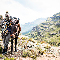22 year old horseman Leputhing Isaac Molapo photographed with his 15 year old horse, Stan. Isaac wears the traditional wooden blanket, rubber boots and balaclava set that is the uniform of all Lesotho horsemen.