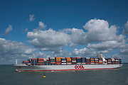 Container ship transporting goods through the Solent near to the Isle of Wight. This large OOCL vessel is stacked high with containers from different companies. This is still the majour way that goods are transported around the World.