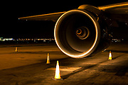 "With traffic cones arranged to avoid accidents in the darkness, the spinning turbofan blades of a British Airways Boeing jet aircraft are highlighted by the headlights of an airfield vehicle during the airliner's overnight turnaround at Heathrow Airport. The beauty of the engine's cowling and the wing to which it is attached shows the marvel of its engineering, of its magnificent aviation design. From writer Alain de Botton's book project ""A Week at the Airport: A Heathrow Diary"" (2009).  Week at the Airport: A Heathrow Diary"" (2009)."