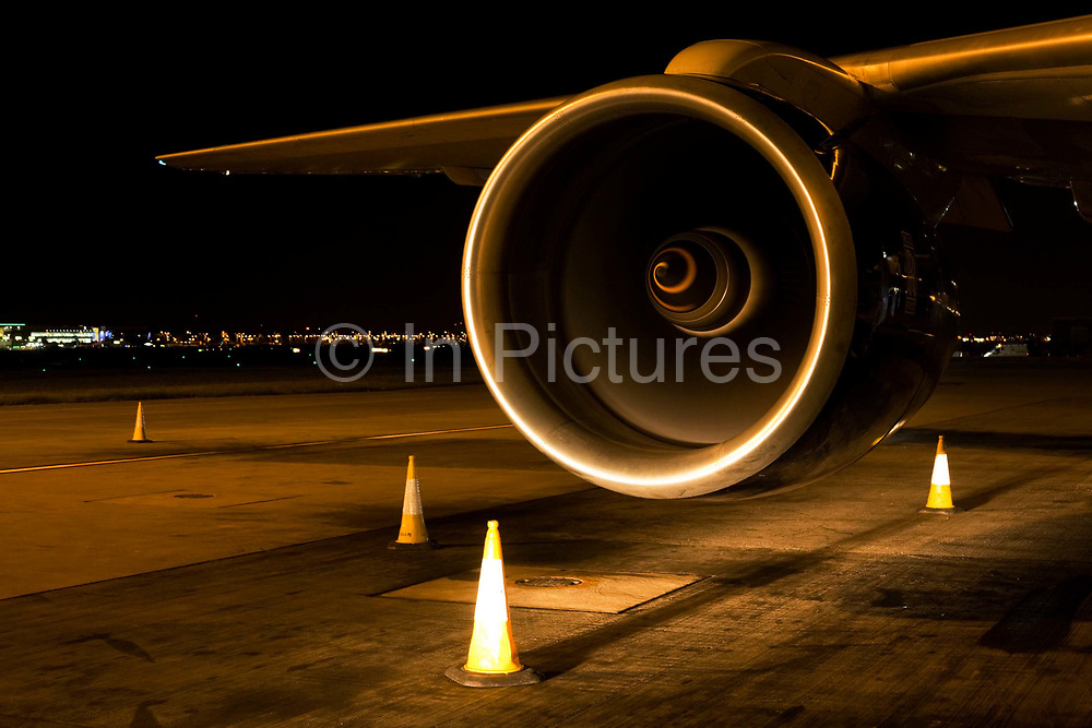 """With traffic cones arranged to avoid accidents in the darkness, the spinning turbofan blades of a British Airways Boeing jet aircraft are highlighted by the headlights of an airfield vehicle during the airliner's overnight turnaround at Heathrow Airport. The beauty of the engine's cowling and the wing to which it is attached shows the marvel of its engineering, of its magnificent aviation design. From writer Alain de Botton's book project """"A Week at the Airport: A Heathrow Diary"""" (2009).  Week at the Airport: A Heathrow Diary"""" (2009)."""
