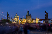 Crowds visiting  Charles Bridge during the evening which is a historic bridge that crosses the Vltava river in Prague and one of the main attractions in the city. Its construction started in 1357 under the auspices of King Charles IV and finished in the beginning of the 15th century.