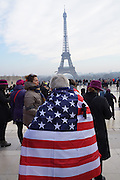January, 21st, 2017 - Paris, Ile-de-France, France: Woman wearing American flag and black ribbon with Eiffel Tower in background. Thousands of protesters in Paris join anti-Trump Women's March around the world.