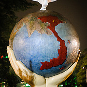 """An art sculpture of a globe with hands and a dove on the shore of Hoan Kiem Lake in Hanoi, Vietnam. The sculpture is titled """"Hope & Love for Peace."""" Night shot."""
