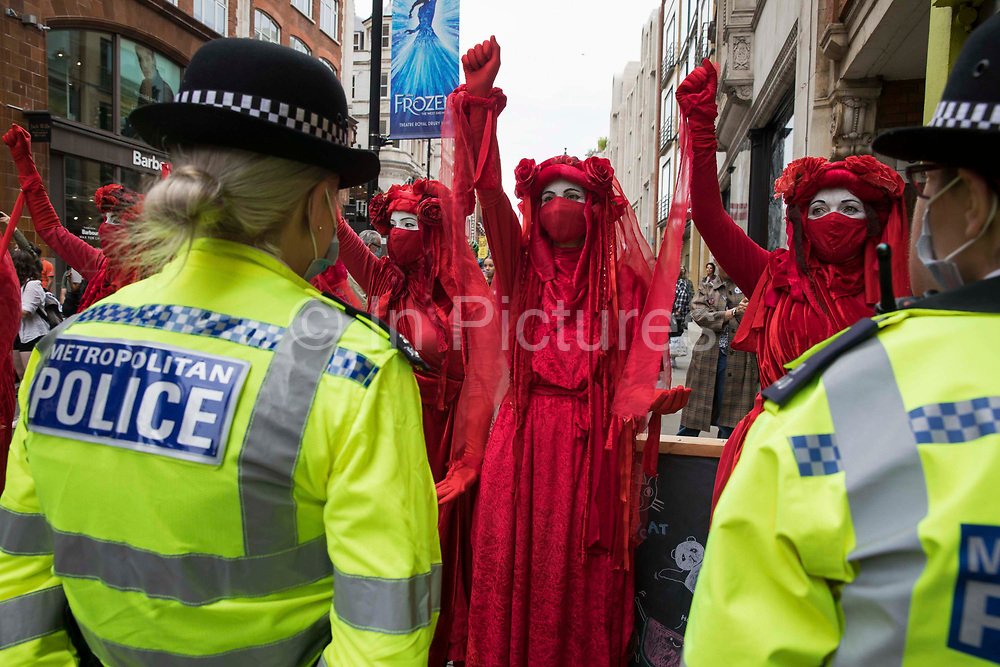 Members of the Extinction Rebellion Red Rebel Brigade raise clenched fists in front of Metropolitan Police officers in the Covent Garden area during the first day of Impossible Rebellion protests on 23rd August 2021 in London, United Kingdom. Extinction Rebellion are calling on the UK government to cease all new fossil fuel investment with immediate effect.