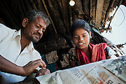 Poonam, 12, (right) is reading a Hindi language newspaper with her father, Suresh Jatev, 45, inside their newly built home in Oriya Basti, one of the water-contaminated colonies in Bhopal, central India, near the abandoned Union Carbide (now DOW Chemical) industrial complex, site of the infamous '1984 Gas Disaster'.