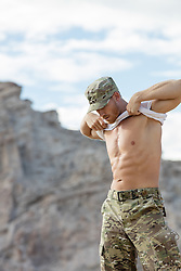 Hot Army man taking off his shirt outdoors