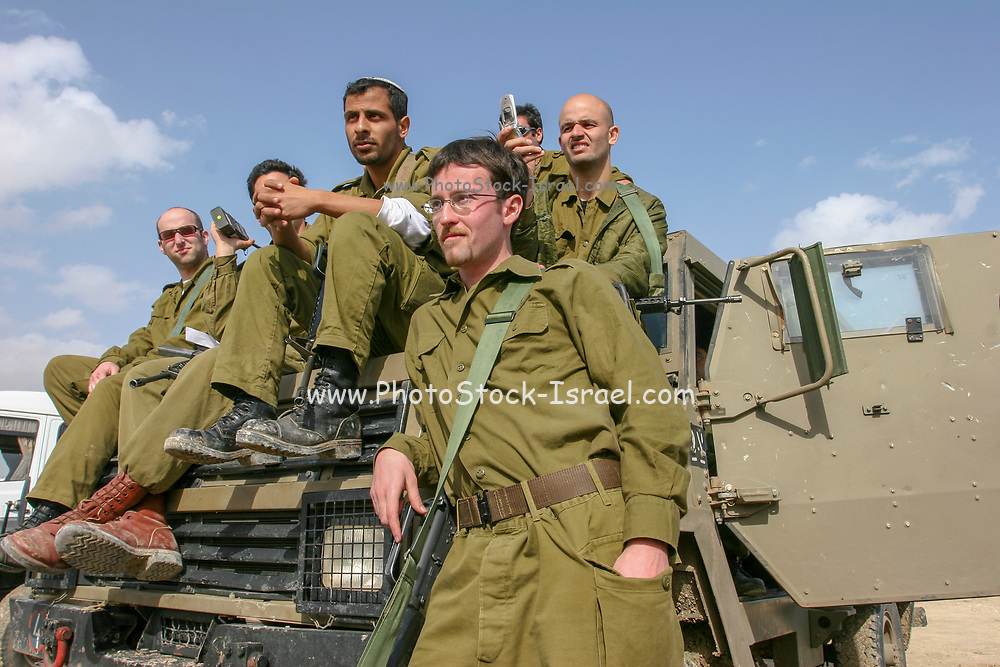 Israeli reserve soldiers on patrol during active duty. sitting on an armoured jeep