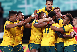 Australia players congratulate Marika Koroibete (centre) after scoring his sixth try during the 2019 Rugby World Cup Pool D match at Sapporo Dome.