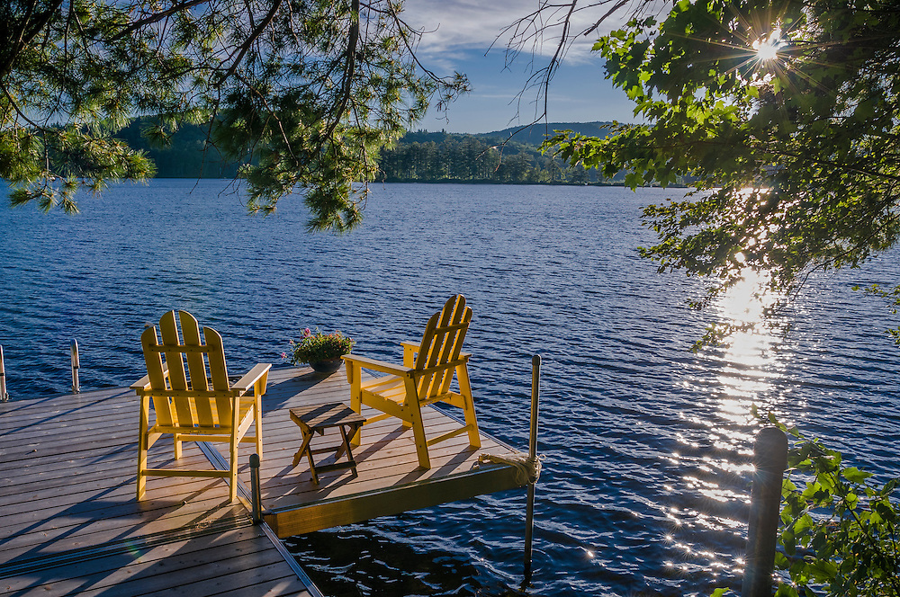 Dock and yellow adirondack chairs at Kezar Lake with late pm sun, North Sutton, NH
