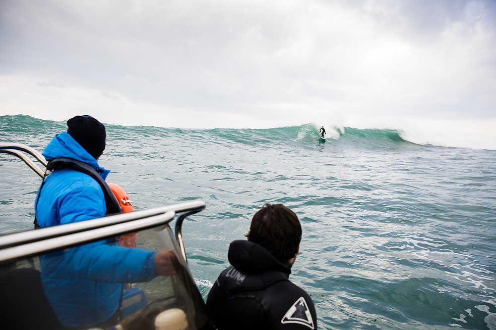 People on a boat watching a man surfing out on the reef in jersey, CI in winter