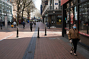 People wearing protective face masks on Corporation Street in Birmingham city centre which is virtually deserted due to the Coronavirus outbreak on 31st March 2020 in Birmingham, England, United Kingdom. Following government advice most people are staying at home leaving the streets quiet, empty and eerie. Coronavirus or Covid-19 is a new respiratory illness that has not previously been seen in humans. While much or Europe has been placed into lockdown, the UK government has announced more stringent rules as part of their long term strategy, and in particular social distancing.