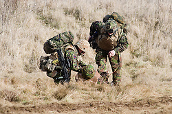 4 Mech Bde taking part in realistic Mission Specific Training on Salisbury Plain Training Area before deployment to Helmand Province Afghanistan. Members of the Royal Dragoon Guards check a simulated battle  casualties condition after pulling him to safety before arranging evacuation by helicopter  9 Feb 2010