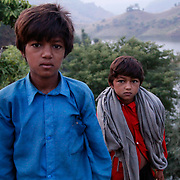Two village boys watch their visitors with curiosity.