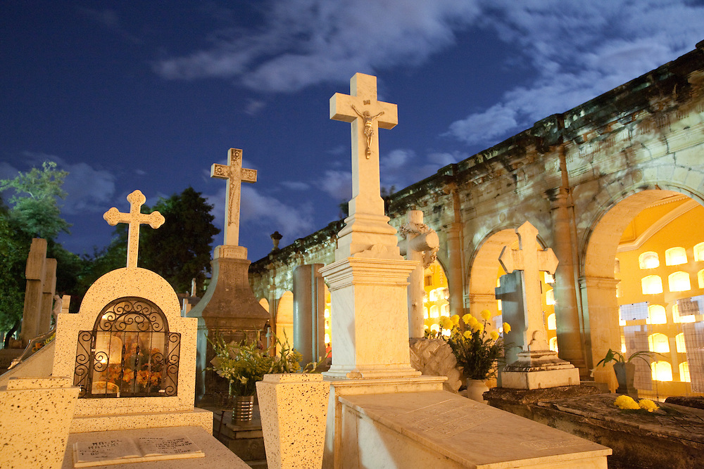 North America, Mexico, Oaxaca Province, Oaxaca, Pantheon San Miguel Cemetery, crosses, graves, and a candle-lit hall at dusk during Day of the Dead (Dias de los Muertos) celebration in November