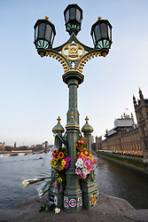 © Licensed to London News Pictures. 24/03/2017. London, UK. Every lamp post on Westminster Bridge carries floral tributes following the terrorist attack in Westminster where five lost their lives and 40 people were injured. Photo credit : Stephen Chung/LNP