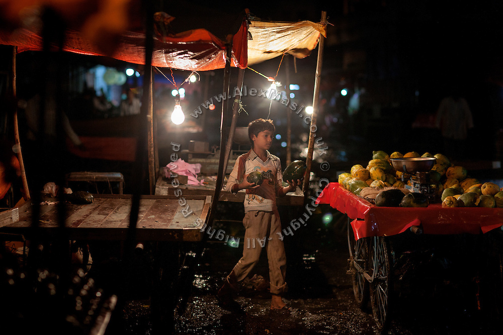 In the late evening, a young boy is loading a wheeled cart with papayas at a market near Hamidia Road in Bhopal, Madhya Pradesh, India.