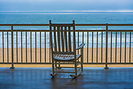 A rocking chair on a terrace overlooking the beach