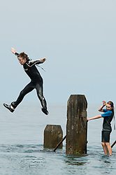 @ Licensed to London News Pictures. 14/07/2013. <br /> Youngsters jumping into the sea from a wooden jetty. People enjoying the continuing hot sunny weather on the beach at the seaside resort of Aberystwyth on the Cardigan Bay coast, West Wales UK. Temperatures in the UK have broken 30 degrees celsius this weekend. Photo credit: Keith Morris/LNP