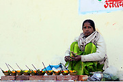 India, Rishikesh. Woman Selling Flower Offerings