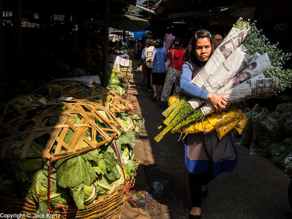 """19 DECEMBER 2013 - BANGKOK, THAILAND:  A woman carries flowers she bought through the flower market. Pak Khlong Talat (""""the market at the mouth of the canal"""") is a market in Bangkok that sells flowers, fruits, and vegetables. It is the primary flower market in Bangkok. It is located on Chak Phet Road and adjacent side-streets, close to Memorial Bridge. The market is open 24 hours, but is busiest before dawn, when boats and trucks arrive with flowers from nearby provinces.      PHOTO BY JACK KURTZ"""