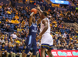 Dec 1, 2019; Morgantown, WV, USA; Rhode Island Rams forward Jermaine Harris (0) shoots over West Virginia Mountaineers forward Oscar Tshiebwe (34) during the first half at WVU Coliseum. Mandatory Credit: Ben Queen-USA TODAY Sports