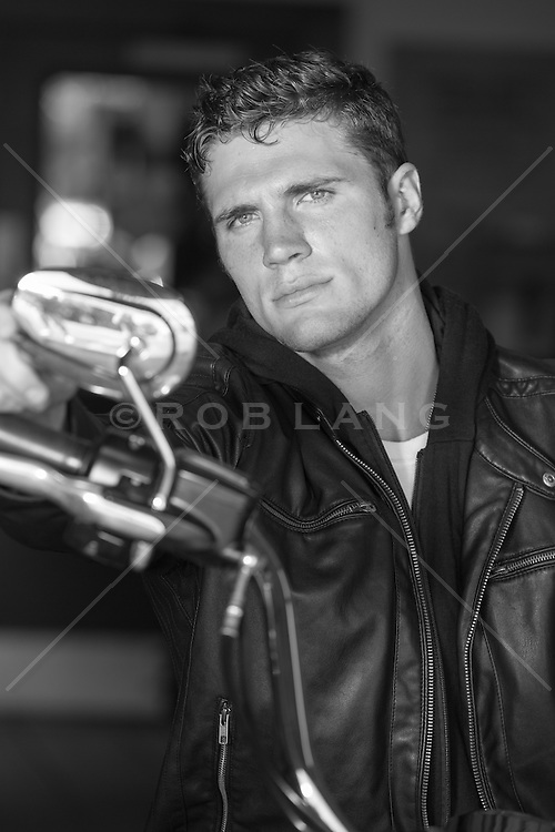 Hot man in a black leather jacket on a motorcycle in a garage looking at himself in a rear view mirror
