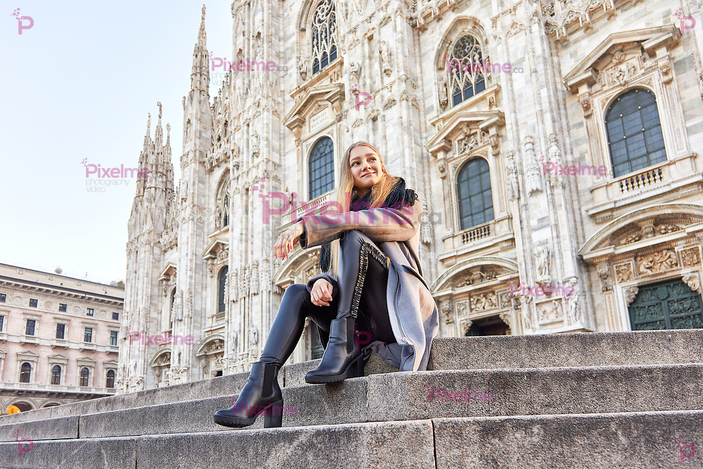 Happy girl sitting and smiling in front of Duomo of Milan Italy during the morning