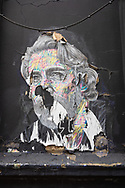 A torn poster showing a male portrait on the side of an empty building in Bloomsbury, London, UK.