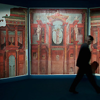 """MILAN, ITALY - JUNE 01:  A Palazzo Reale employee walks in front of a murals of """"Second Pompeian Style"""", dating from 100 years BC, at """"I due Imperi"""" exhibition on June 1, 2010 in Milan, Italy. The Exhibition illustrates the birth and development of the Roman Empire and the Empire of the Chinese Qin and Han Dinasties  (Photo by Marco Secchi/Getty Images)"""