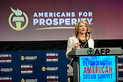 """PERSON speaks during the """"Defending the American Dream Summit"""" hosted by Americans For Prosperity at the Omni Hotel in Dallas, Texas on August 29, 2014. (Cooper Neill for The New York Times)"""