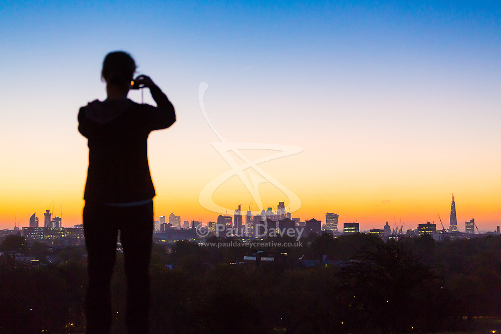London, October 27 2017. A woman takes a picture as the day breaks over London's skyline, seen from Primrose Hill. © Paul Davey