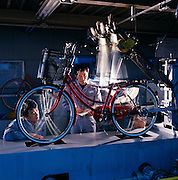 Company inspectors spot-check bicycles for durability.  Here one of its mass-produced bikes is subjected to the simulated pounding of a spin on a bumpy road.