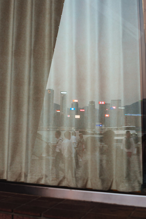 The Hong Kong Island skyline and people walking along Tsim Sha Tsui waterfront, are reflected in a window of the Hong Kong Cultural Centre, in Tsim Sha Tsui, Kowloon, Hong Kong, China, on September 25, 2019.
