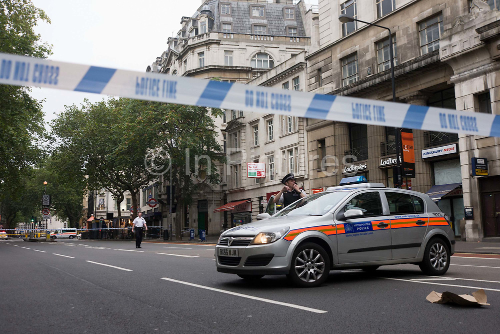 Suspect packages have been found outside premises in Central London, a situation urgent enough to warrant the closure of Holborn and surrounding streets in case the items are terrorist-related. The subsequent evacuation of commuters at a time when thousands of office workers were making their way out of their company buildings towards the London Underground station ahead on the right. A policeman uses is radio to communicate with senior officers The force are taking no chances from abandoned rubbish left at will in public places - their efforts that may save lives from explosive terrorist devices, such as bombs. With streets emptied during the busiest time of the day, the police have control of the area while around the corner, experts inspect the problem before re-opening to the public.