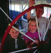 Model released three children holding paddle steamer boat wheel, Australia